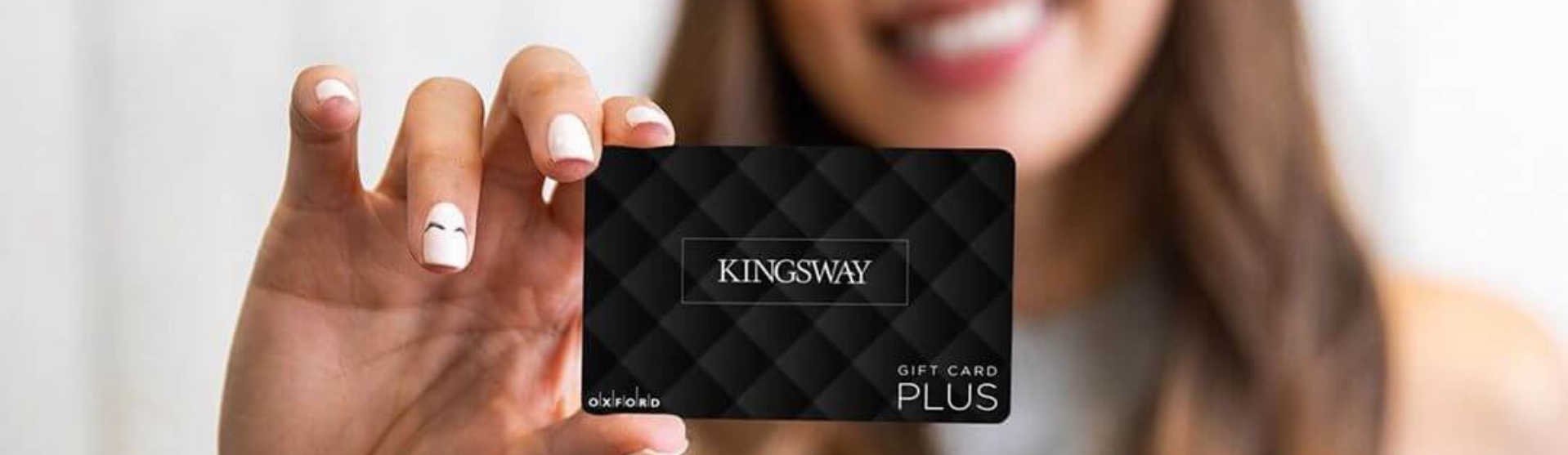 Woman holding up a gift card
