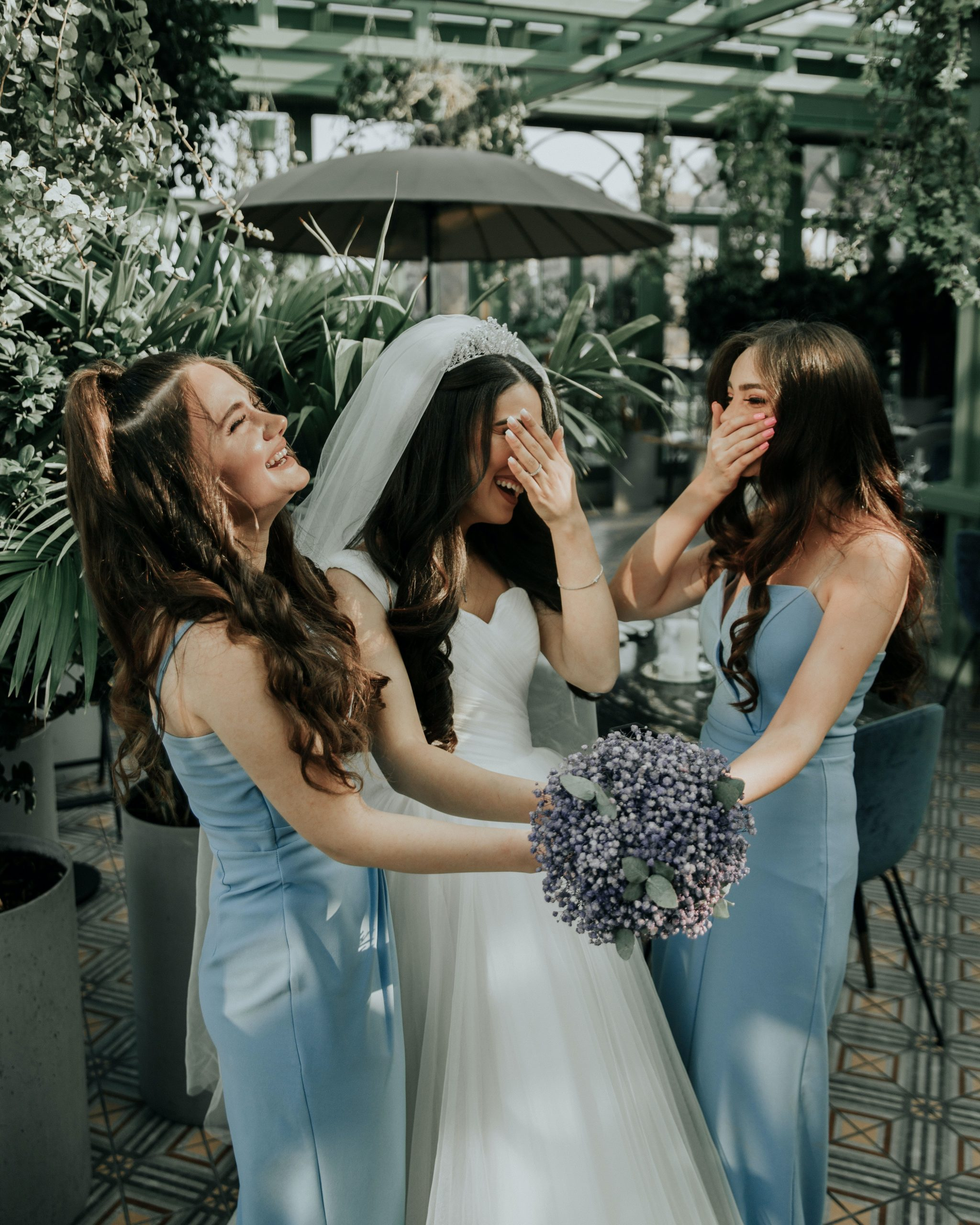 A bride and 2 bridesmaids laughing