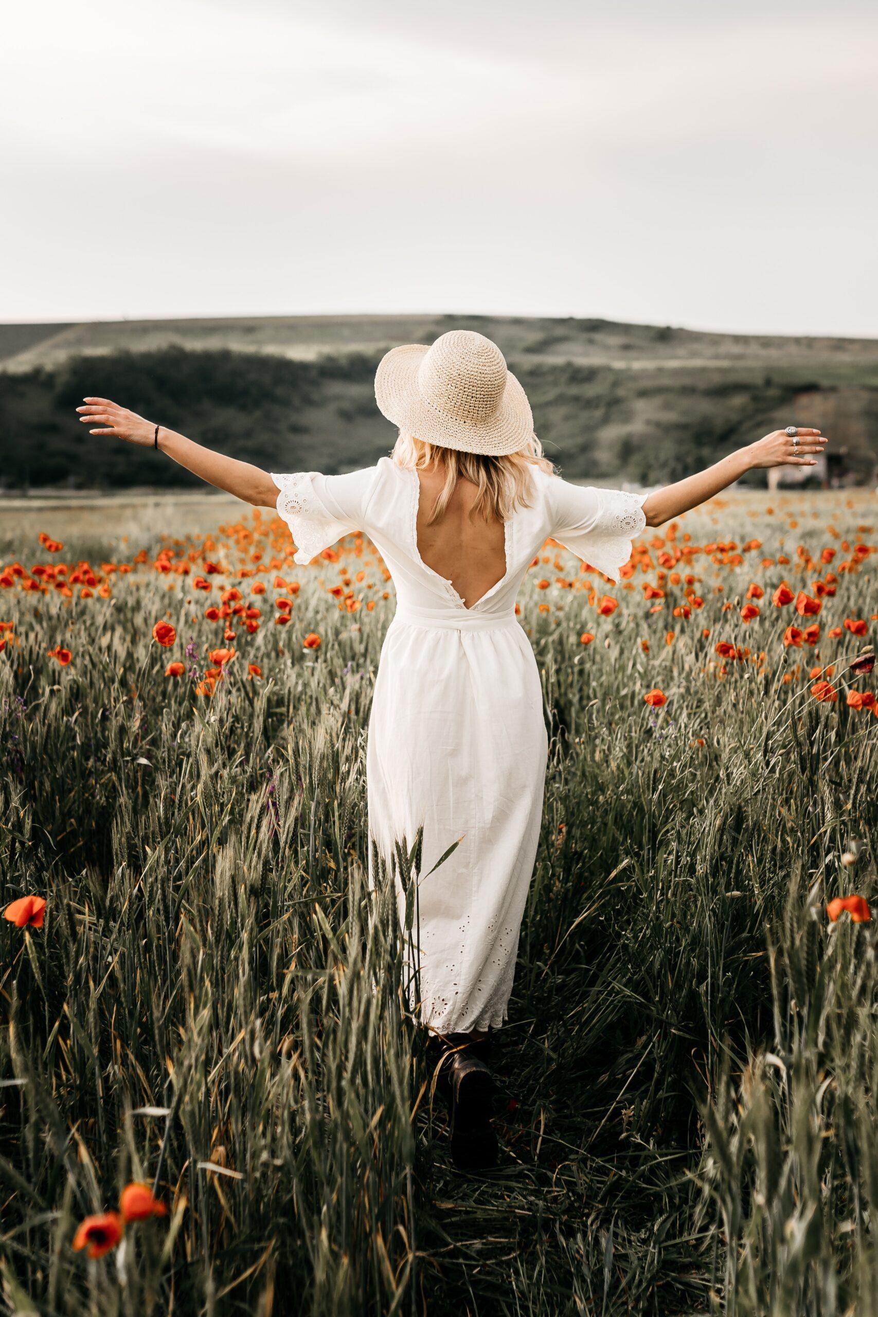 Girl in a white dress walking through a field