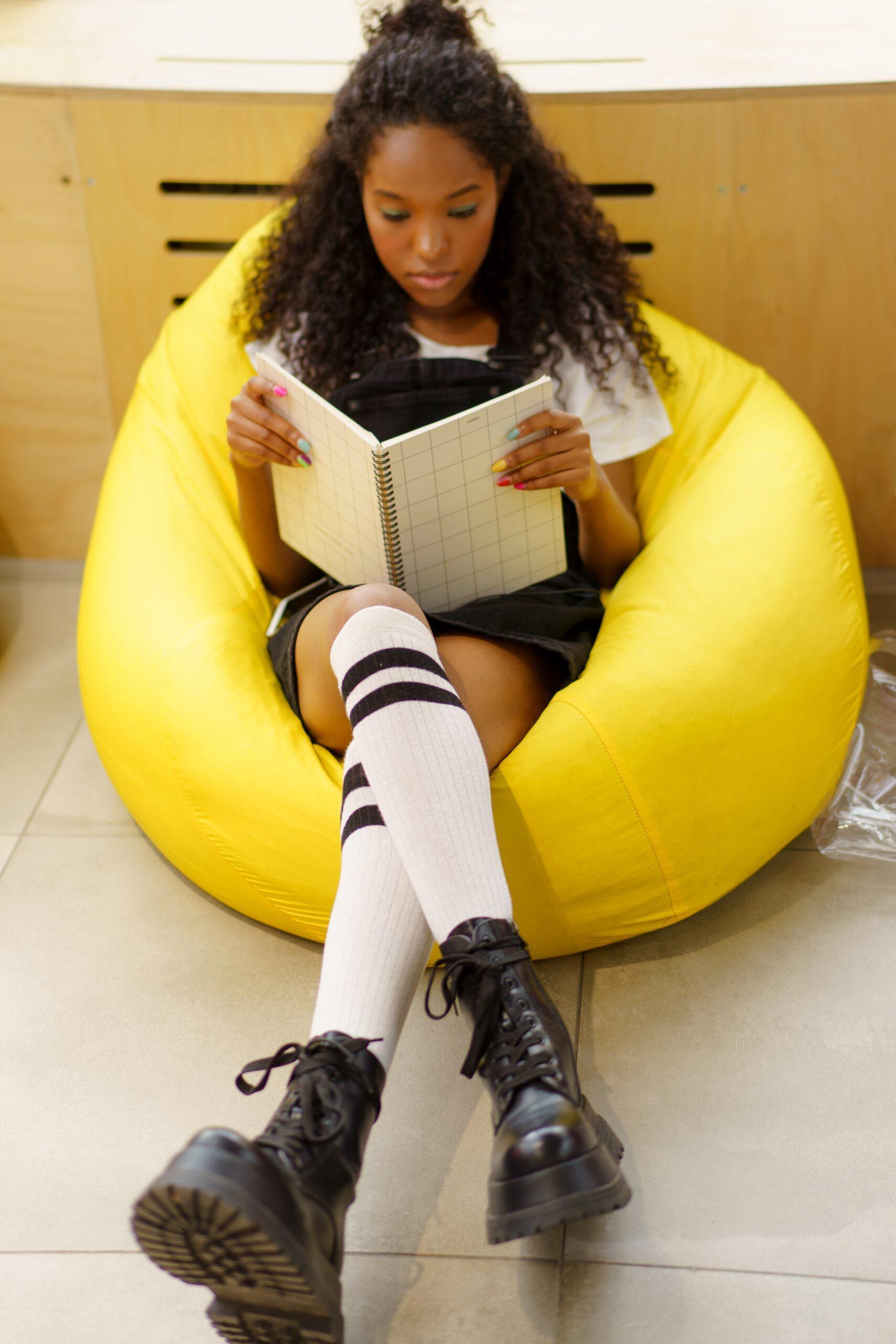 Girl reading a book in a bean bag