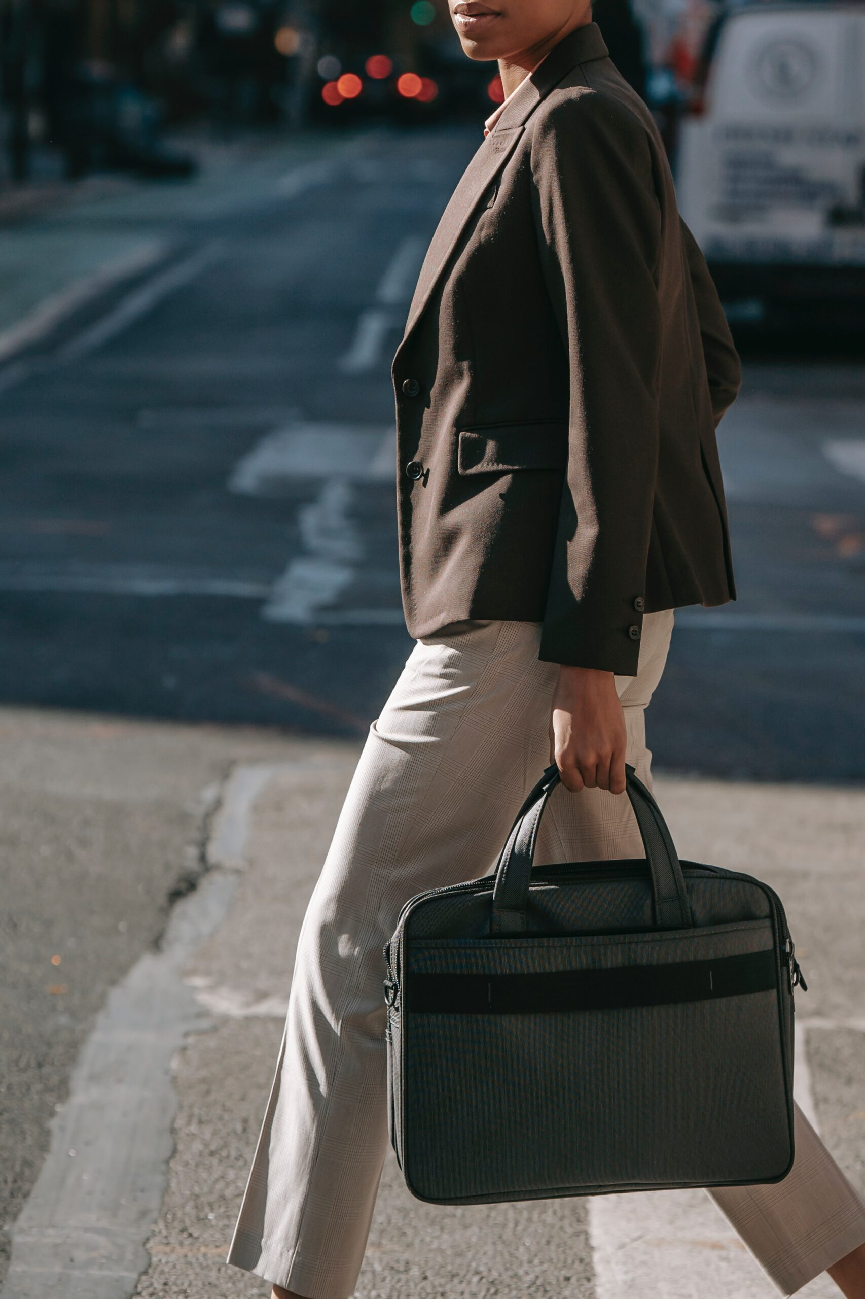 Woman walking across the street in business attire and brief case