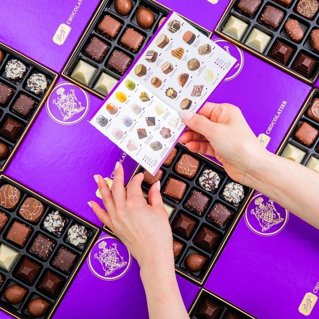 Hand reaching for a box of chocolates