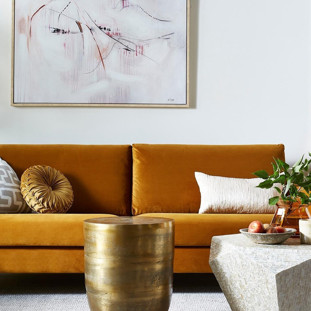 Orange velvet couch with a gold round coffee table