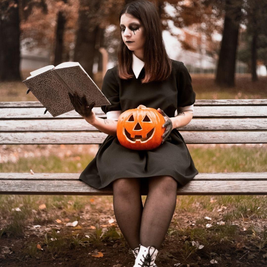 Girl in a black dress holding a pumpkin